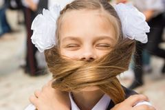 The schoolgirl on holiday on September 1 covered her face with her long hair. The schoolgirl on a holiday on September 1 covered her face with her long hair stock photos