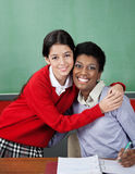 Schoolgirl Hugging Female Teacher At Desk Stock Photos