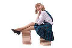 Schoolgirl Is Sitting On The Stack Of Book. Royalty Free Stock Image