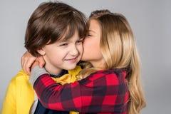 Schoolgirl kissing in cheek schoolboy Stock Image