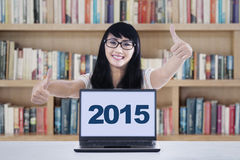 Schoolgirl with laptop showing thumbs-up in library. High school student with numbers 2015 on laptop computer and giving thumbs-up, shot in the library Stock Photo