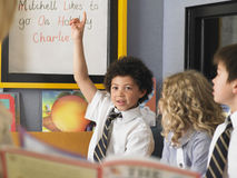 Schoolgirl Laughing With Boys In Classroom Stock Photo