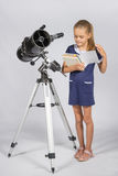 Schoolgirl leafing through a textbook while standing at the telescope royalty free stock photo