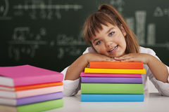 Schoolgirl leaning on books Royalty Free Stock Images