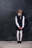 Schoolgirl leaning her forehead against blackboard Stock Photography