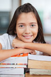Schoolgirl Leaning On Stack Of Books In Classroom Royalty Free Stock Photography