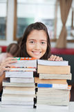 Schoolgirl Leaning On Stack Of Books In Classroom. Portrait of cute little schoolgirl leaning on stack of books at desk in classroom Stock Images