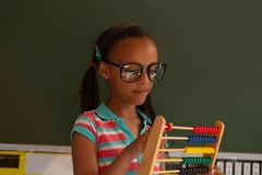 Schoolgirl learning mathematics with abacus in the classroom stock photos