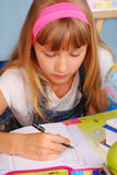Schoolgirl learning to write. Schoolgirl in the classroom learning to write alphabet  by pen in the notebook Royalty Free Stock Photo