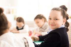 Schoolgirl at lesson. Portrait of cute schoolgirl sitting among her classmates and drawing during a lesson Stock Image