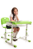 Schoolgirl on lesson. Young cheerful smiling schoolgirl sitting at the desk on lesson Royalty Free Stock Images