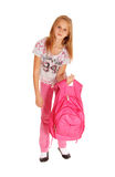 Schoolgirl lifting heavy backpack. Royalty Free Stock Image