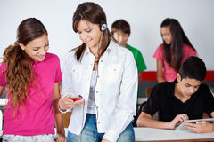 Schoolgirl Listening Music While Showing. Teenage schoolgirl listening music while showing mobilephone to classmate in classroom Royalty Free Stock Photography