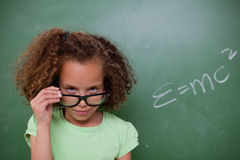 Schoolgirl looking above her glasses Stock Images