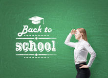 Schoolgirl is looking through the air. Words ' back to school ' are written on the green chalkboard. Royalty Free Stock Photography