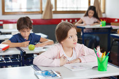 Schoolgirl Looking Away While Drawing In Classroom Stock Photography