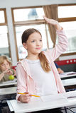 Schoolgirl Looking Away While Raising Hand In Royalty Free Stock Images