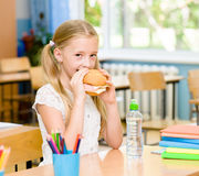 Schoolgirl looking at camera while having lunch during break Stock Photography