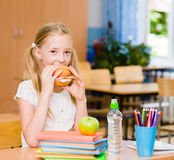 Schoolgirl looking at camera while having lunch during break Stock Photos