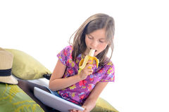 Schoolgirl looking at a digital tablet and eat fruit Stock Image
