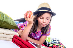 Schoolgirl looking at a digital tablet and eat fruit Stock Photography