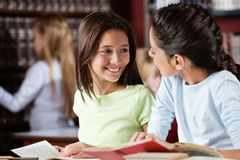 Schoolgirl Looking At Female Friend In Library. Happy little schoolgirl looking at female friend while studying in library Stock Images