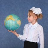 Schoolgirl looking at a geographical globe Royalty Free Stock Photography