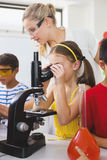 Schoolgirl looking through microscope in laboratory Royalty Free Stock Images