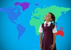 Schoolgirl looking up in front of colorful world map Stock Photos
