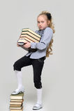 Schoolgirl and a lot of books. Young schoolgirl and a lot of books Royalty Free Stock Image
