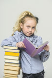 Schoolgirl and a lot of books Stock Photography