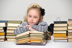Schoolgirl and a lot of books. Young schoolgirl and a lot of books Royalty Free Stock Photography