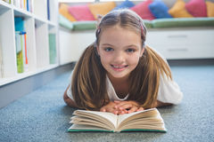 Schoolgirl lying on floor and reading a book in library Stock Images