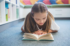 Schoolgirl lying on floor and reading a book in library Royalty Free Stock Image