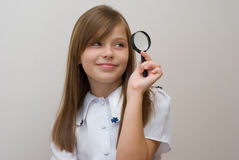 Schoolgirl with a magnifier Royalty Free Stock Images