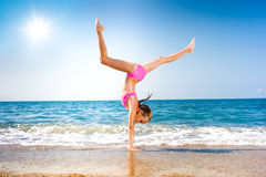 Schoolgirl making gymnastics on seashore or beach Royalty Free Stock Photos