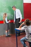 Schoolgirl And Male Teacher Looking At Each. Little schoolgirl and male teacher looking at each other standing by greenboard in classroom Royalty Free Stock Photo