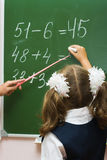 The schoolgirl at a mathematics lesson. The girl solves examples at a lesson at a school board Royalty Free Stock Images