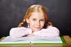 Schoolgirl med en bok royaltyfri bild