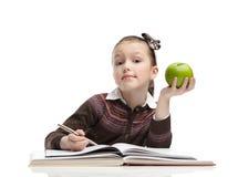 Schoolgirl med ett grönt äpple royaltyfri foto