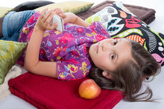 Schoolgirl with a mobile phone, lying on the floor Royalty Free Stock Photos