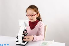 Schoolgirl with modern microscope Royalty Free Stock Images