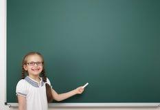 Schoolgirl near school board Stock Images