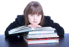 Schoolgirl. Nice schoolgirl in black uniform sitting at a table in front of her stack of books she reads Stock Photo