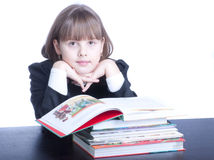Schoolgirl. Nice clever  schoolgirl in black uniform sitting at a table in front of her stack of books she reads Royalty Free Stock Images