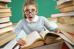 Schoolgirl with open mouth look at camera. Photo of little girl sitting at the desk with open book. Education concept Royalty Free Stock Photography