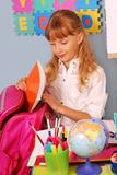 Schoolgirl packing her backpack Royalty Free Stock Photos