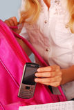 Schoolgirl packing her mobile phone stock image