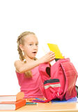 Schoolgirl packing her rucksack Royalty Free Stock Photos