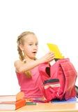 Schoolgirl packing her rucksack royalty free stock photos